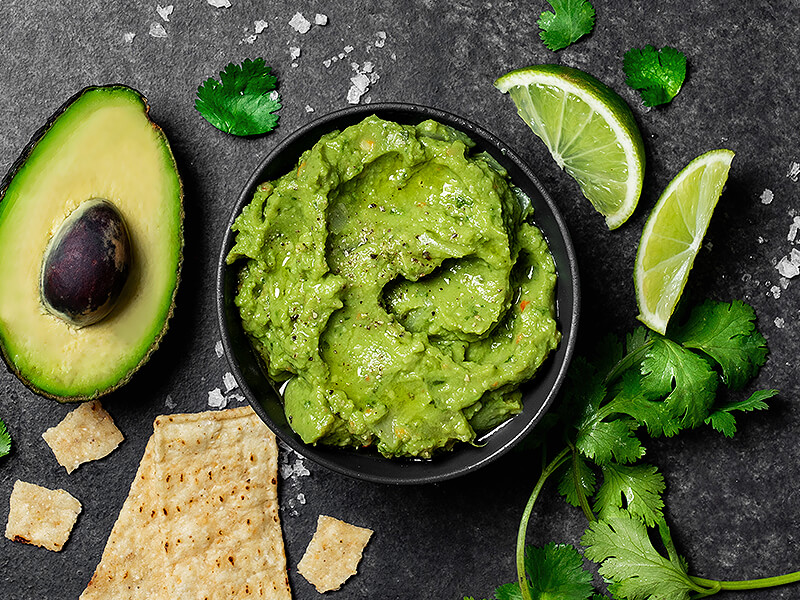 Small bowl of guacamole with scattered lime wedges and corn chips