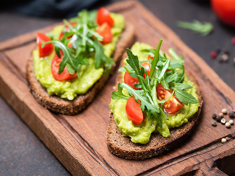 Smashed avocado on toast with tomato and rocket